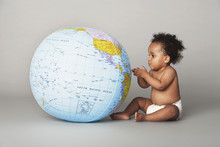 Full Length Of Baby Girl Looking At Inflatable Globe Isolated On Gray Background