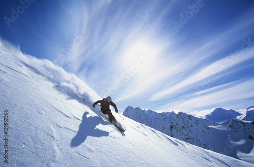 Full length of skier skiing on fresh powder snow Wallpaper Mural