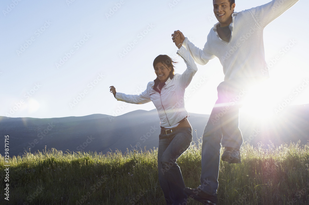 Fototapety, obrazy: Happy young multiethnic couple jumping while holding hands in park