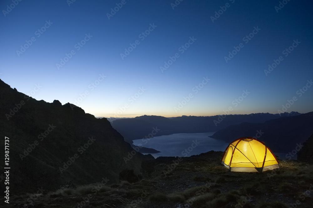 Fototapety, obrazy: Illuminated tent by the lakeshore at dusk
