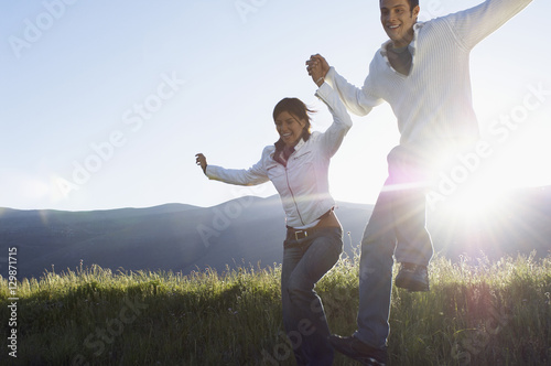 Fotografia  Happy young multiethnic couple jumping while holding hands in park