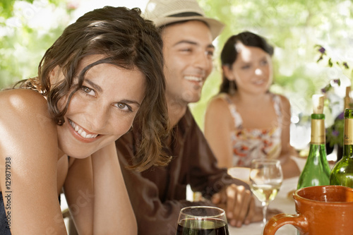 Photographie  Portrait of beautiful young woman with friends enjoying drinks at party