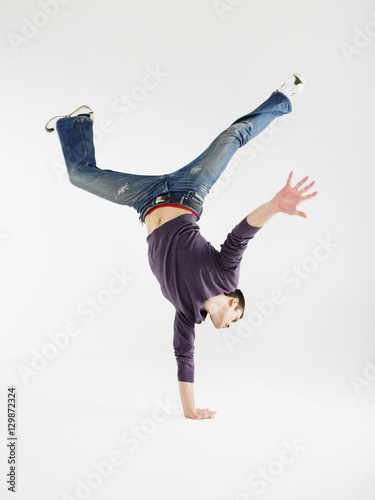 Photo Full length of a young man doing one handed handstand against gray background
