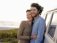 Smiling Young Couple Embracing By Campervan On Beach