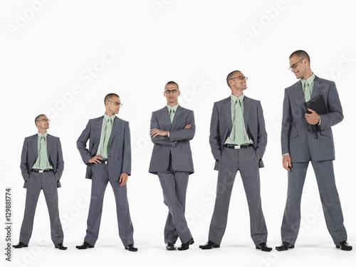 Valokuva  Row of businessmen in ascending order of height against white background