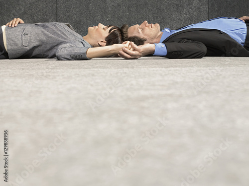 Fototapeta Side view of young businessman and businesswoman holding hands while lying on ground obraz na płótnie