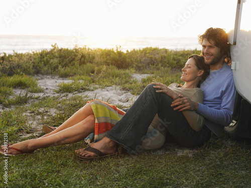 Photo  Full length of young couple on beach leaning on campervan