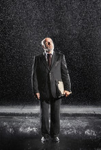Full Length Of A Middle Aged Businessman With Binder Standing In The Rain
