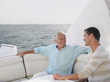 Happy Senior Man With Son Relaxing On Yacht