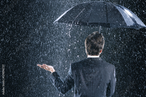 Платно Rear view of a businessman staying dry under umbrella during downpour