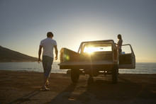 Full Length Of Young Couple By Pick-up Truck Parked On Beach