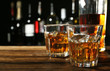 Glasses of whisky on wooden bar closeup