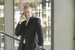Happy middle aged businessman using cell phone in office