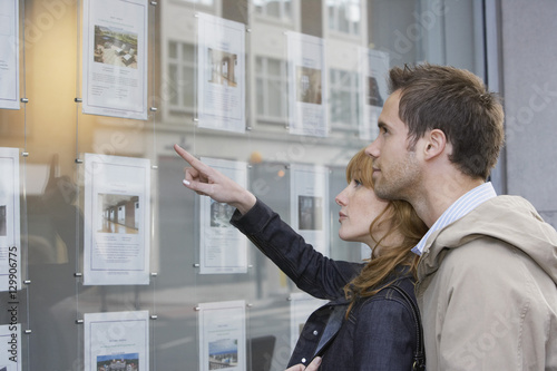 Fotografía  Side view of a young couple looking at window display at real estate office