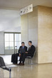 Two businessmen using laptop in the airport lobby