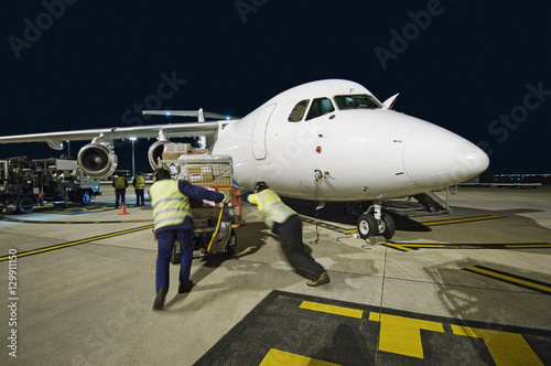 Fotografie, Obraz  Airfreight loading onto BAE-146 at night.