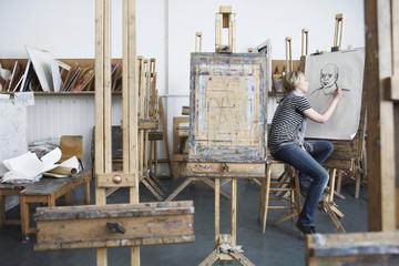 Puna dužina bočni pogled mlade studentice koja crta portret ugljena u umjetničkom studiju na fakultetu