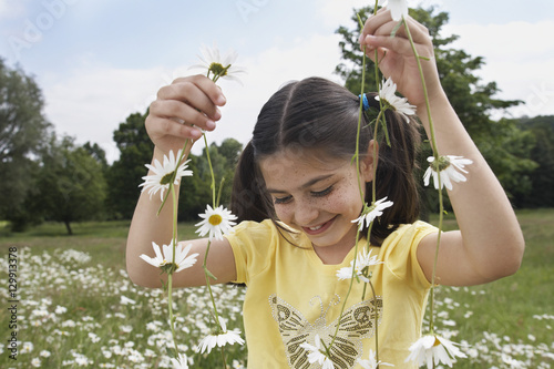 Fotografia, Obraz  Smiling young girl holding daisy chains in meadow