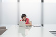 Beautiful casual young woman using laptop in modern cubicle at office