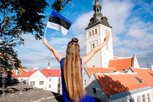 Fototapeta premium Młoda turystka z estońską flagą przed kościołem świętego Mikołaja na starym mieście w Tallinie. Kobieta na wspaniałych wakacjach w Estonii