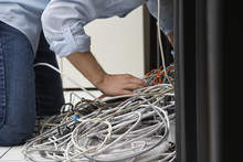 Side View Of A Man Working On Tangled Computer Wires In Office