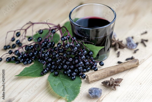 Glass of fresh elderberry syrup with ingredients