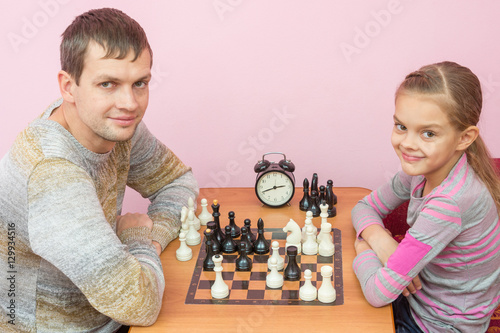 Photo  Dad and daughter playing chess with a smile and looked into the frame