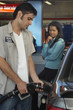 Businesswoman looking at gas station attendant pumping fuel into car