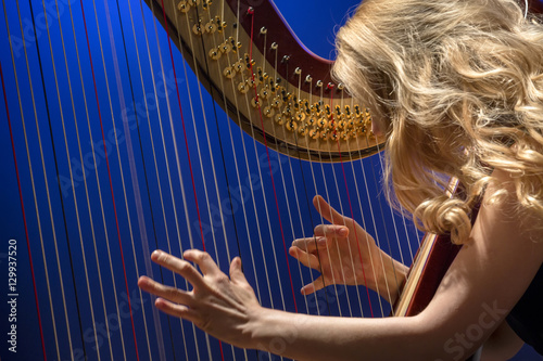 Fotografía Closeup portrait of young girl playing the harp during concert at musical theate