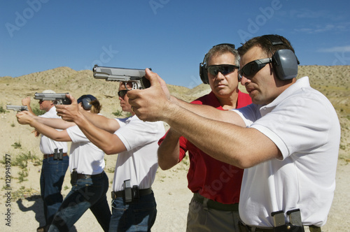 Fotomural  Instructor assisting officers with hand guns at firing range during weapons trai