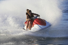 Young Couple Enjoying The Ride Of Personal Watercraft On Lake