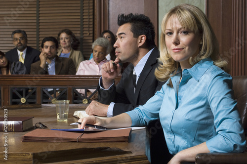 Obraz na plátne Portrait of a female defense lawyer sitting with client in court room