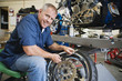 Portrait of a happy male mechanic working on a tire at workplace