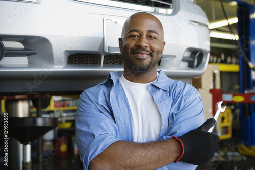plakat Portrait of a confident African American male mechanic holding wrench at garage
