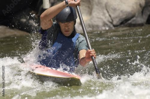 Valokuva  Young man whitewater kayaking on mountain river