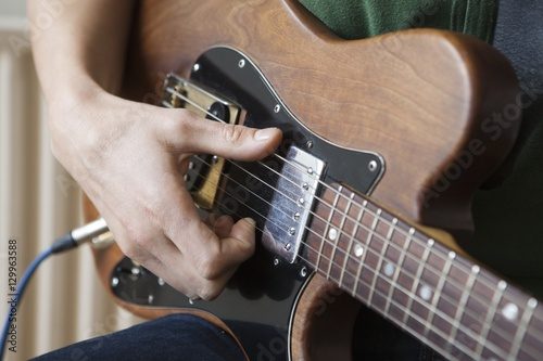 Fototapeta Closeup of a young man strumming chord on guitar