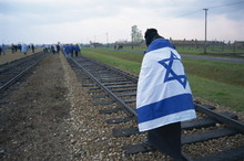 Youngster Wrapped In Flag Walking On Rail, Birkenau Concentration Camp, Oswiecim, Malopolska, Poland