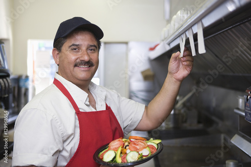 Tableau sur Toile Portrait of Hispanic Latin man with served food standing in restaurant kitchen
