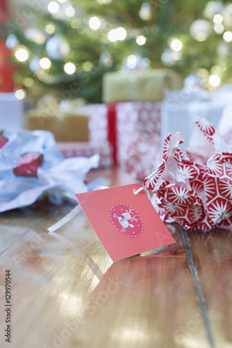 Fotografia, Obraz  Unwrapped gift paper and tag on hardwood floor with Christmas tree in background