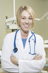 Portrait of a confident female dentist with arms crossed and stethoscope in clinic