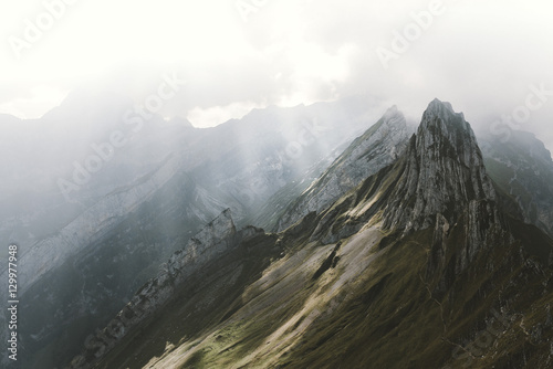 Mountain range in the alps with dramatic sky and rays of light - 129977948