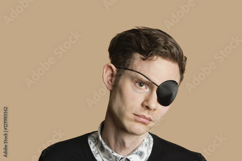 Fotografia Sad mid adult man wearing eye patch over colored background