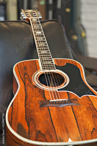 Poster Muziekwinkel Close-up view of acoustic guitar lying on sofa in music store