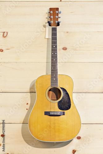 Spoed Foto op Canvas Muziekwinkel Martin guitar hanged against wood grain wall