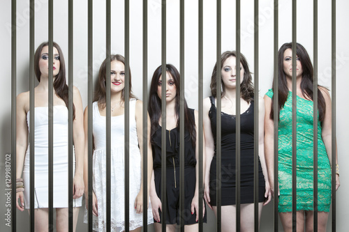 Fotografía  Portrait of five young women standing side by side behinds prison bars