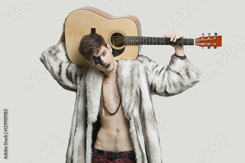 Obraz na plátně  Portrait of young male guitarist in fur coat holding guitar over shoulder agains