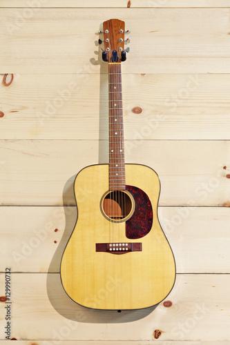 Spoed Foto op Canvas Muziekwinkel Steel-string acoustic guitar on wood grain wall