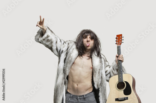 Valokuva  Young man in fur coat holding guitar while gesturing over gray background