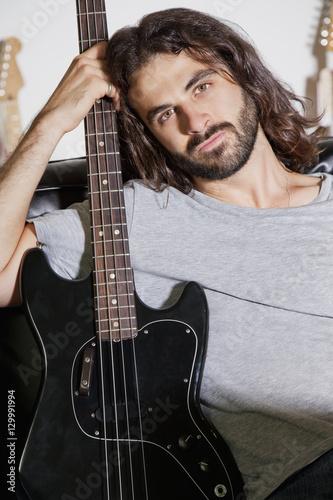 Spoed Foto op Canvas Muziekwinkel Portrait of young man holding guitar