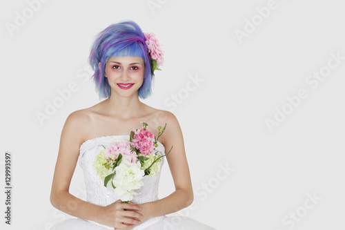 Valokuva  Portrait of happy young woman in wedding dress with dyed hair against gray backg